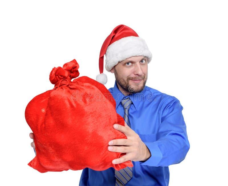 Uomo barbuto nel cappello di Santa Claus ed in borsa rossa piena dei regali, isolati su fondo bianco fotografie stock libere da diritti