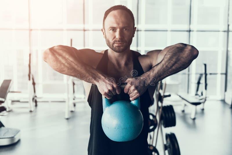 Uomo barbuto nell'addestramento della camicia nel club di forma fisica fotografie stock