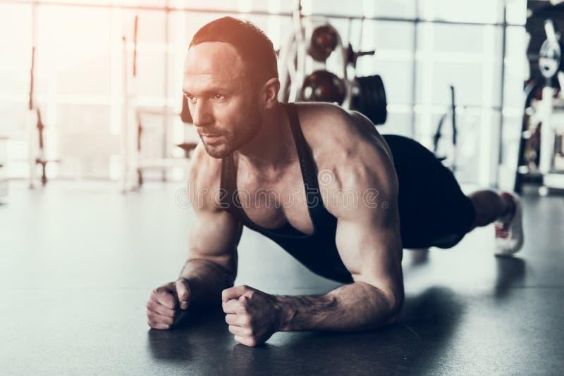 Uomo barbuto nell'addestramento della camicia nel club di forma fisica immagini stock libere da diritti