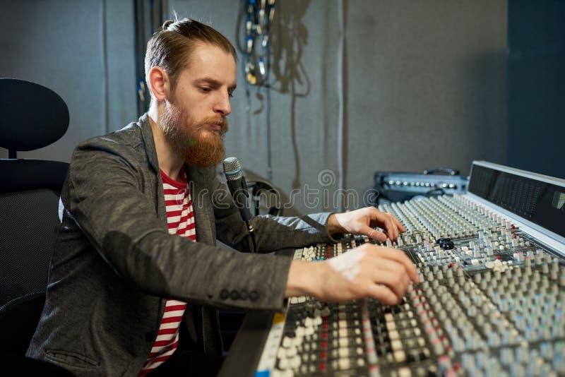 Uomo barbuto nello studio di registrazione di musica immagine stock