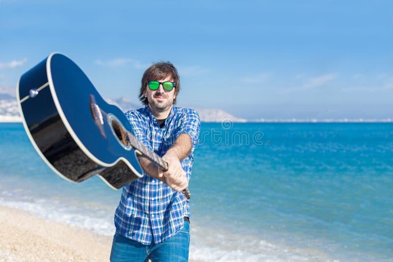 Uomo barbuto in occhiali da sole con la chitarra sulla spiaggia immagine stock libera da diritti