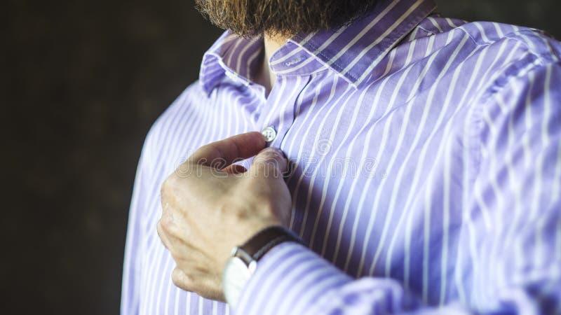 Uomo barbuto in orologio che abbottona la sua camicia immagini stock