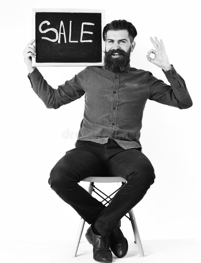 Uomo barbuto, pantaloni a vita bassa caucasici brutali con l'iscrizione di vendita della tenuta dei baffi fotografia stock libera da diritti