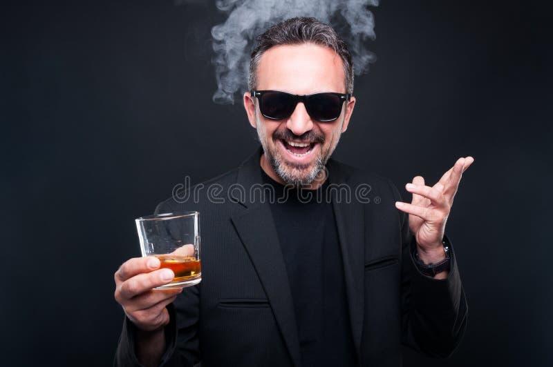 Uomo barbuto ricco alla moda che gode di un brandy immagini stock libere da diritti
