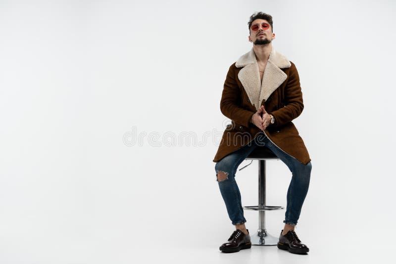 Uomo barbuto serio in vestiti alla moda casuali ed occhiali da sole rossi che si siedono sullo sgabello da bar, esaminante la mac fotografie stock libere da diritti