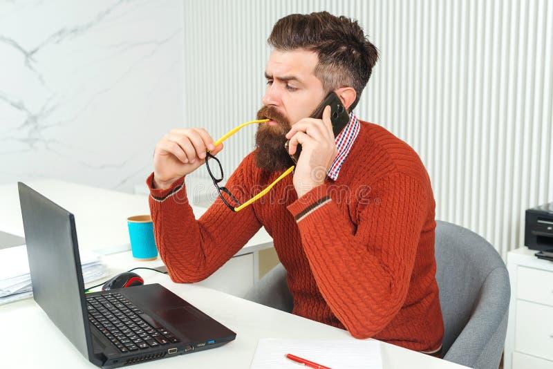 Uomo barbuto sicuro che lavora al computer portatile Uomo che comunica sul telefono mobile Tipo barbuto al suo posto di lavoro in immagine stock libera da diritti