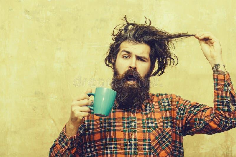 Uomo barbuto sorpreso che tira i capelli alla moda della frangia con la tazza blu fotografia stock