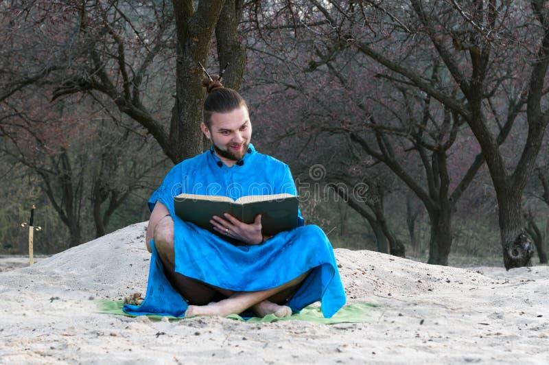 Uomo barbuto sorpreso in kimono blu che si siede con il grande libro sulla spiaggia sabbiosa immagine stock libera da diritti