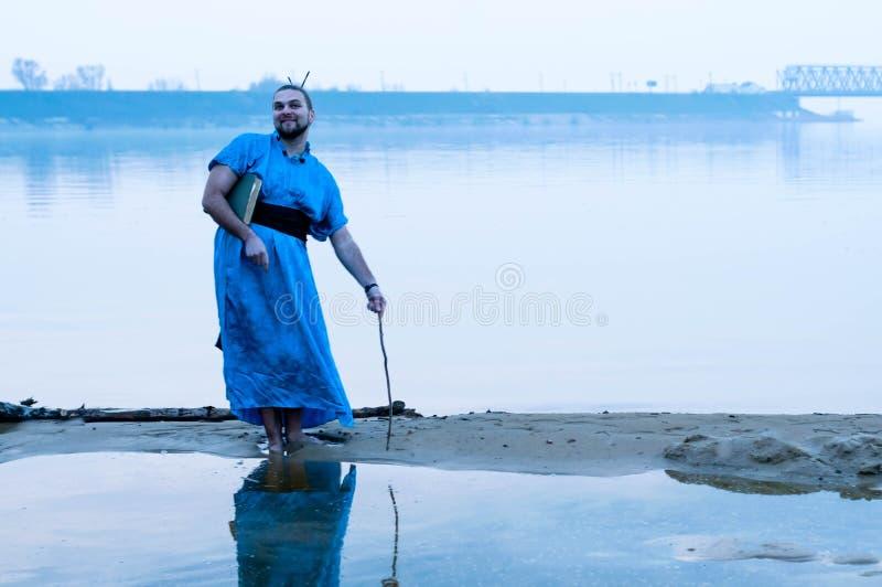 Uomo barbuto sorridente nella condizione blu del kimono sulla sponda del fiume in nebbia con il bastone di legno fotografie stock