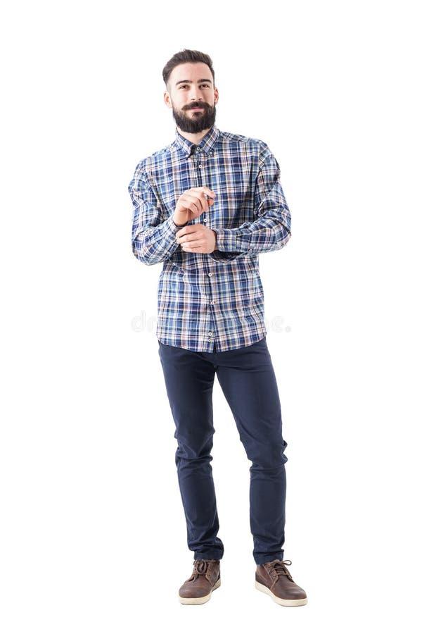 Uomo barbuto sorridente sicuro di affari che si veste abbottonando manica ed esaminando macchina fotografica fotografia stock