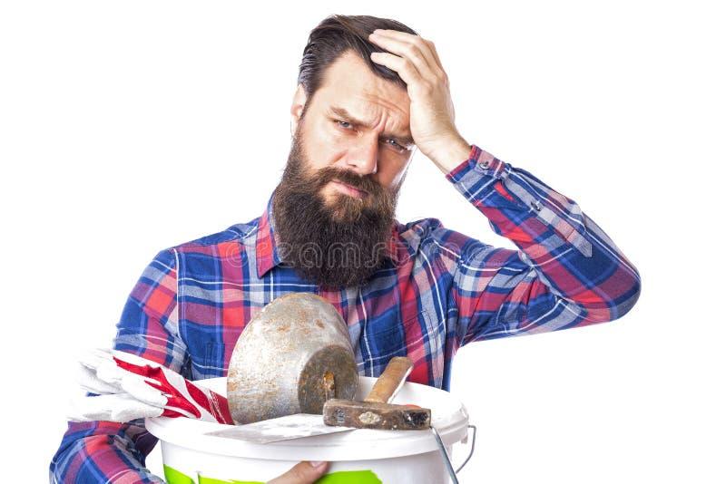 Uomo barbuto triste che tiene gli strumenti utilizzati della muratura immagini stock