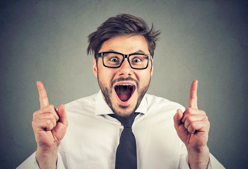 uomo barbuto in vetri che indica su con le dita che esaminano stupite e felici la macchina fotografica su fondo grigio immagine stock