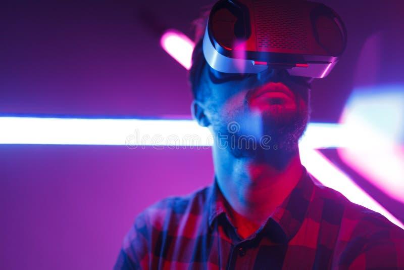 Uomo barbuto in VR contro l'ardore al neon fotografia stock