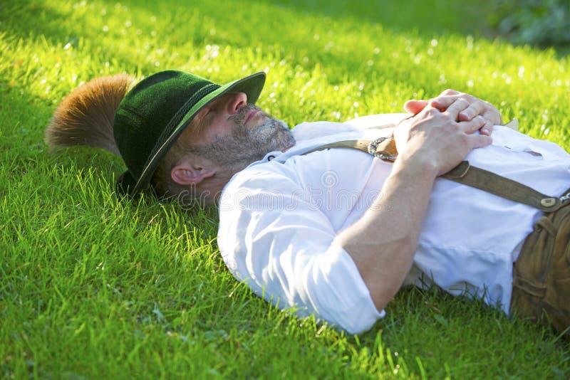 Uomo bavarese che dorme sull'erba immagine stock
