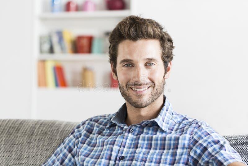 Uomo bearbed allegro dei pantaloni a vita bassa in casa moderna bianca Macchina fotografica del fronte immagini stock