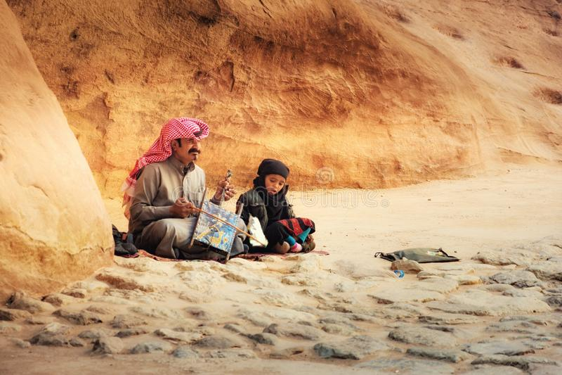 Uomo beduino che gioca gli strumenti musicali tradizionali della corda di Rababa del beduino con suo figlio in città antica di PE immagini stock libere da diritti