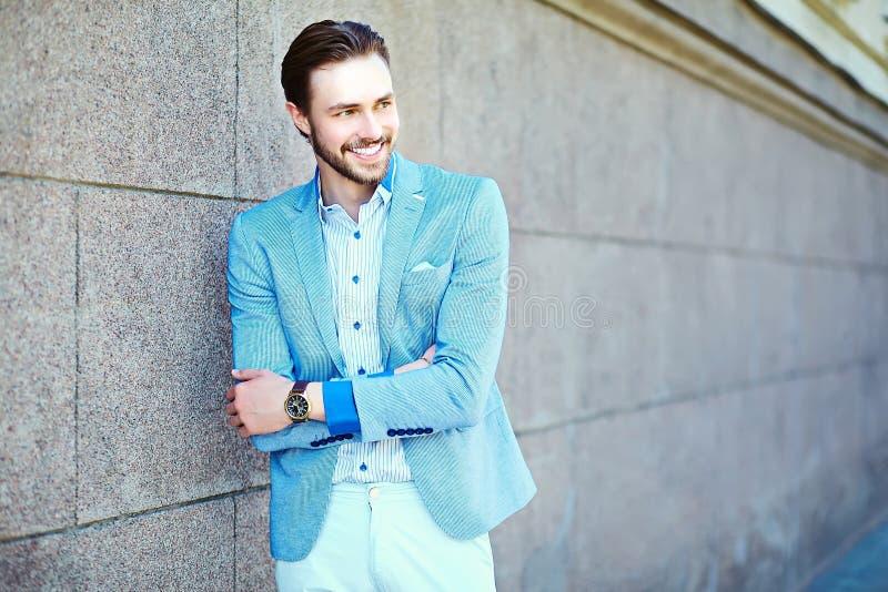 Uomo bello alla moda sorridente in vestito nella via immagine stock