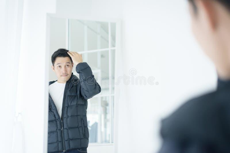 Uomo bello asiatico che lo esamina in specchio all'interno fotografia stock libera da diritti