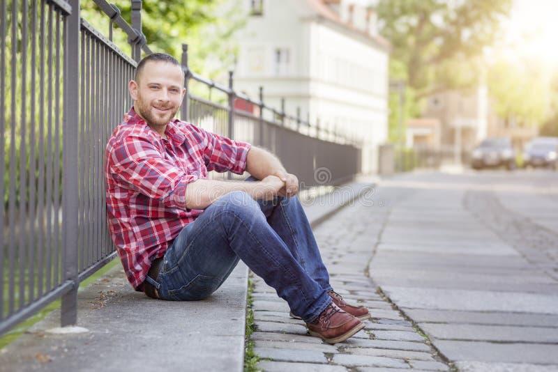 Uomo bello barbuto che si rilassa alla via fotografia stock libera da diritti