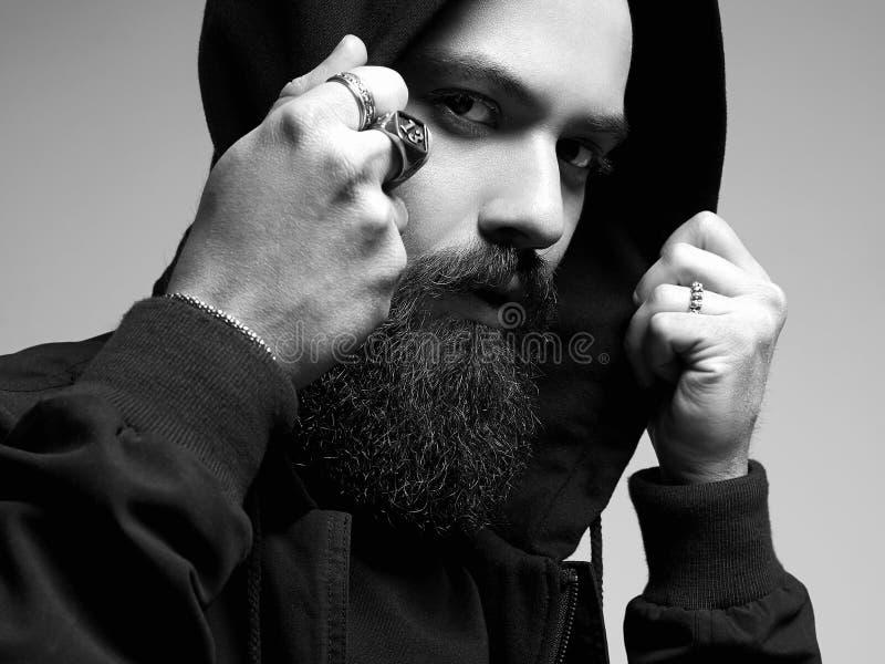 Uomo bello barbuto sotto il cappuccio nero Ragazzo alla moda immagine stock libera da diritti