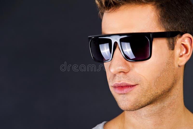 Uomo bello in canottiera sportiva grigia con il sorriso e gli occhiali da sole immagini stock libere da diritti