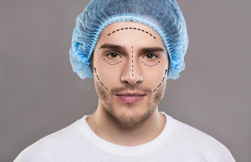 Uomo bello in cappello medico con i segni della matita su pelle immagini stock