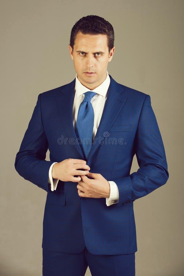 Uomo bello che abbottona bottone sul rivestimento convenzionale blu elegante del vestito fotografie stock libere da diritti