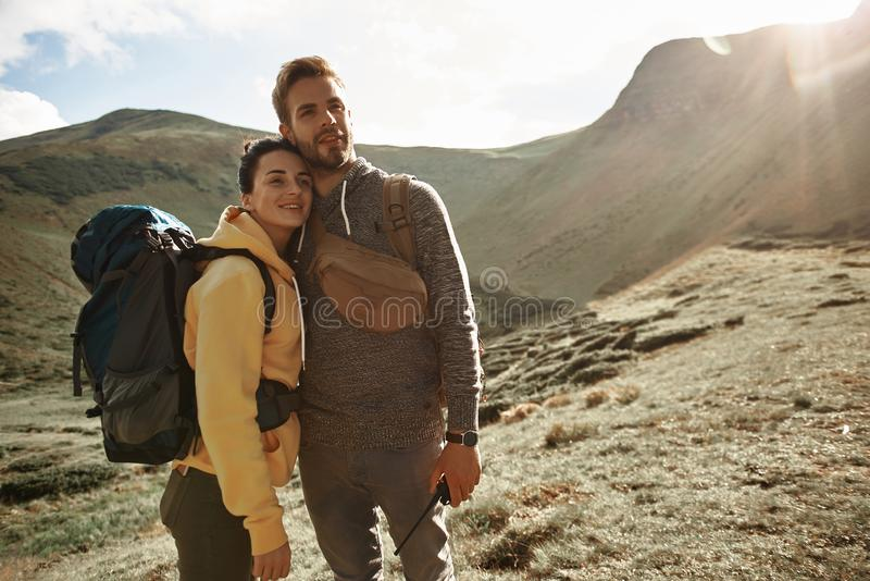 Uomo bello che abbraccia giovane donna mentre viaggiando con lei immagine stock libera da diritti