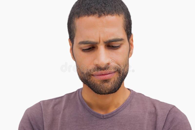 Uomo bello che aggrotta le sopracciglia e che guarda giù fotografia stock libera da diritti