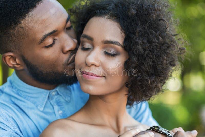 Uomo bello che bacia tenero la sua amica in guancia immagine stock libera da diritti