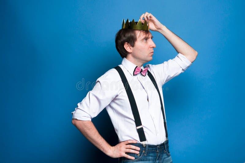 Uomo bello che distoglie lo sguardo e che corregge corona dorata sulla testa su fondo blu fotografie stock