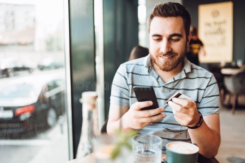 Uomo bello che effettua un pagamento sullo smartphone facendo uso della carta di credito Concetto mobile di acquisto immagini stock libere da diritti