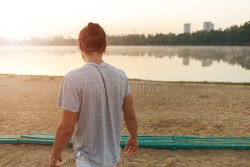 Uomo bello che esamina l'alba nel parco sul lacke fotografia stock