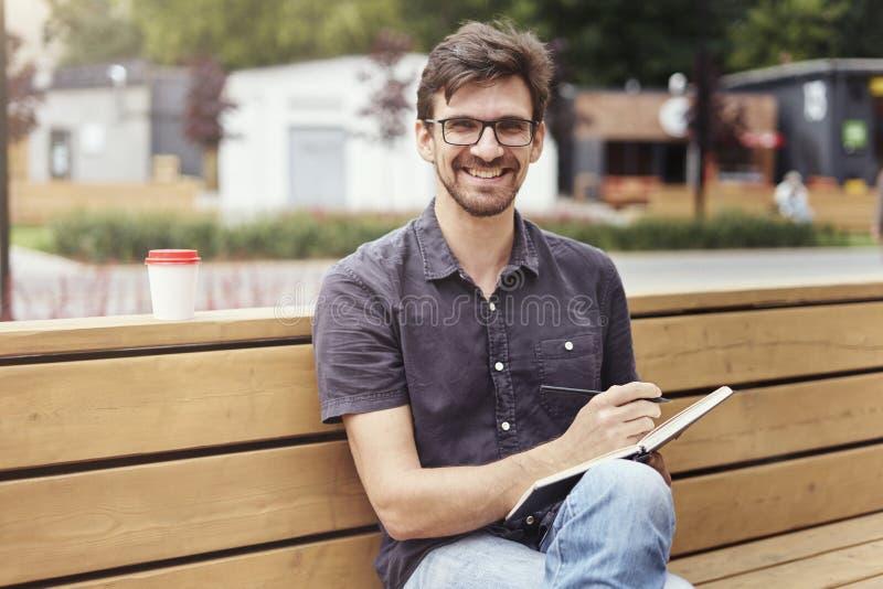 Uomo bello che fa le note in un libro che si siede fuori Lavoro solo d'uso sorridente di vetro del fronte Concetto degli studenti fotografie stock