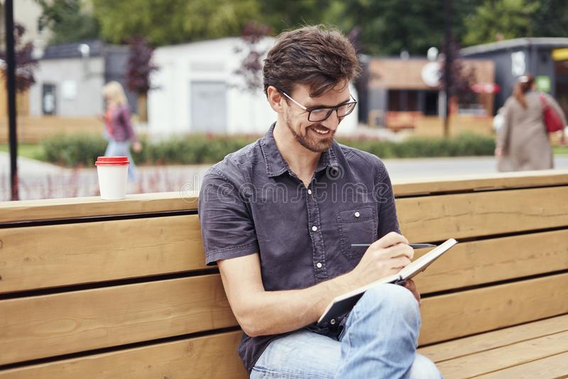 Uomo bello che fa le note in un libro che si siede fuori Lavoro solo d'uso sorridente di vetro del fronte Concetto degli studenti fotografia stock libera da diritti