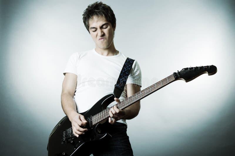 Uomo bello che gioca sulla chitarra immagini stock