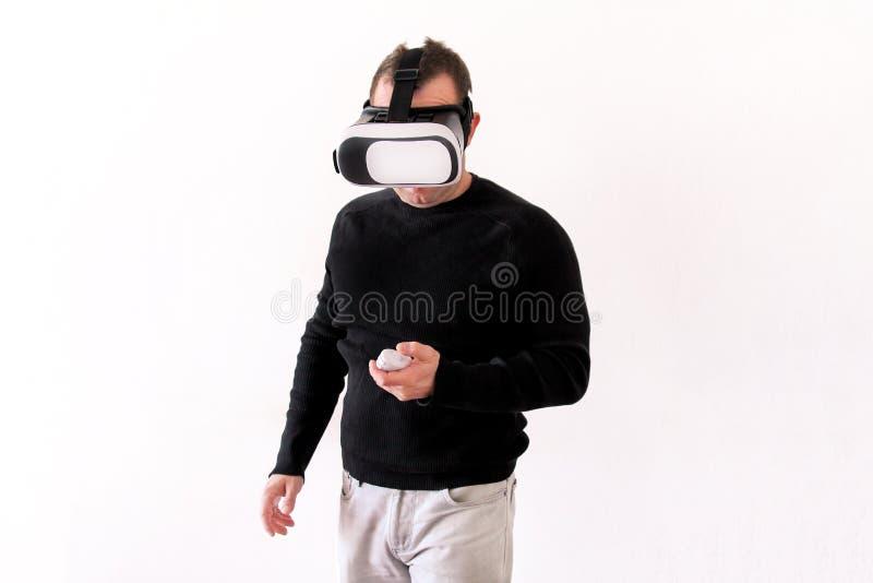 Uomo bello che indossa e che gioca realtà virtuale su fondo bianco isolato Azione del ragazzo nel casco di realtà virtuale Vetri  immagini stock libere da diritti