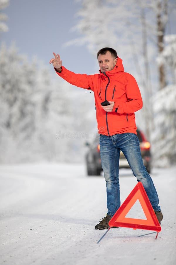 Uomo bello che installa un triangolo d'avvertimento e che richiede l'assistenza dopo che la sua automobile ripartita fotografia stock libera da diritti