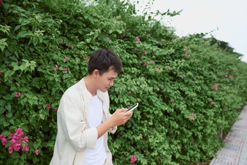 Uomo bello che manda un sms sul telefono cellulare mentre camminando nel parco verde immagini stock