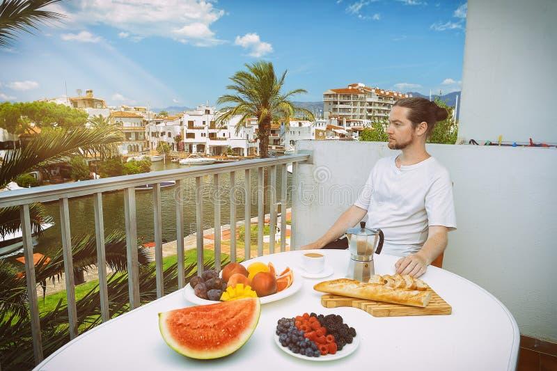Uomo bello che mangia prima colazione sana sul terrazzo dell'hotel fotografie stock