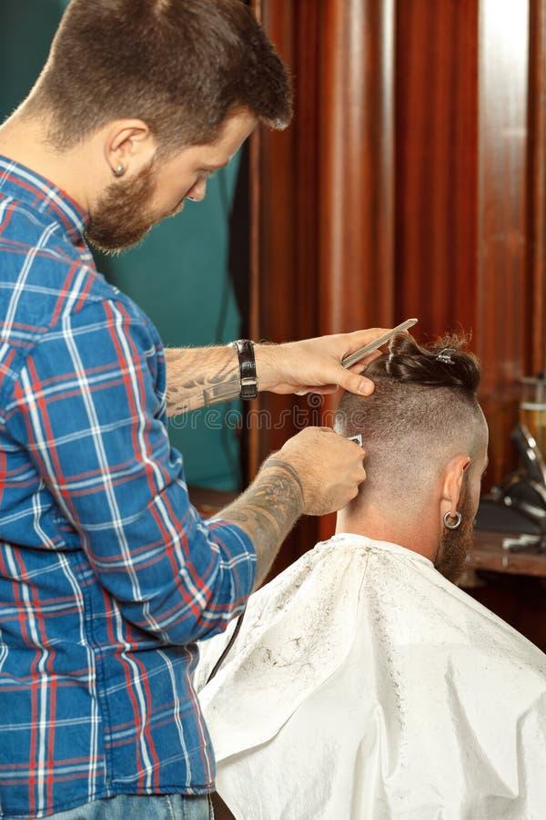 Uomo bello che ottiene nuovo taglio di capelli in un negozio di barbiere fotografie stock libere da diritti