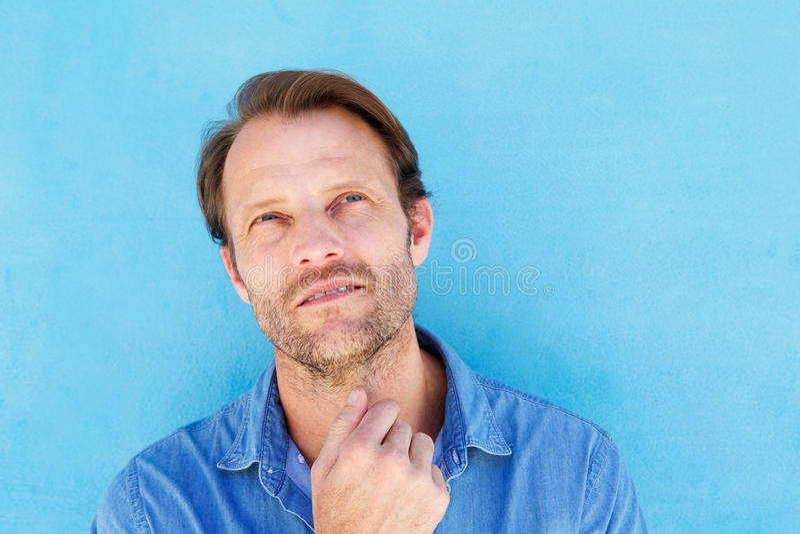 Uomo bello che pensa con la mano al mento contro la parete blu fotografie stock