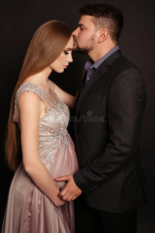 Uomo bello che posa con la donna incinta splendida immagine stock