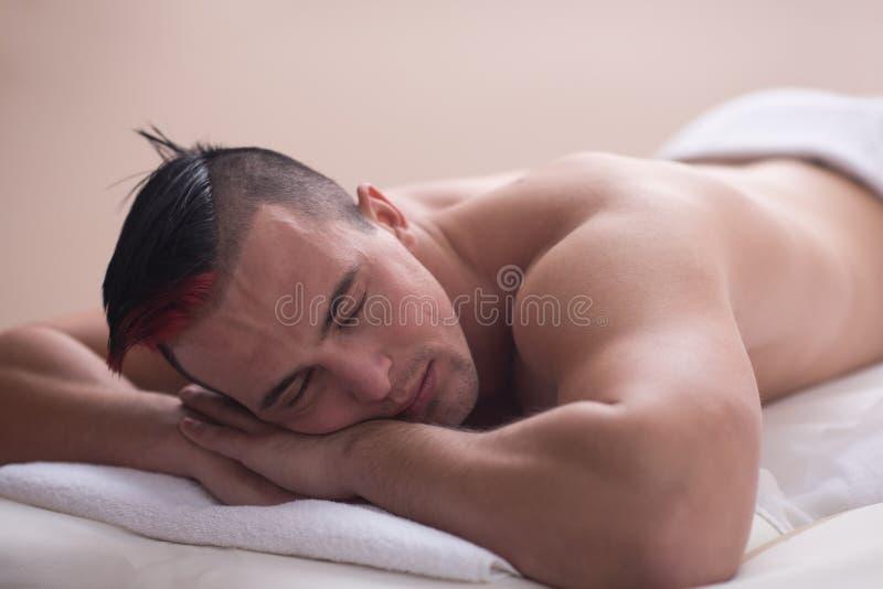 Uomo bello che riposa in un centro di massaggio della stazione termale fotografia stock