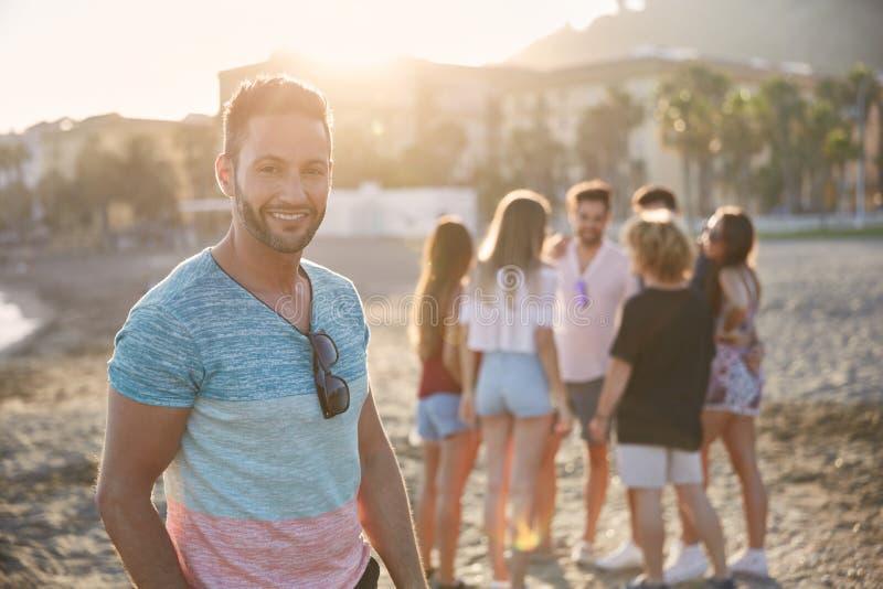 Uomo bello che sta sulla spiaggia con suo sorridere degli amici immagini stock