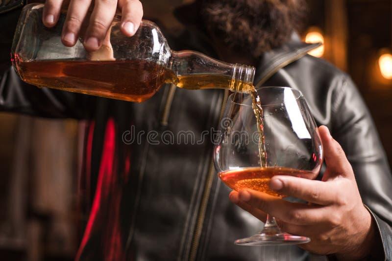 Uomo bello che tiene un vetro di whiskey Whiskey sorseggiante Degustation, assaggio Uomo che tiene un vetro di whiskey fotografia stock
