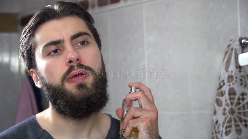 Uomo bello che usando profumo davanti allo specchio Uomo bello che applica profumo alla mattina immagine stock