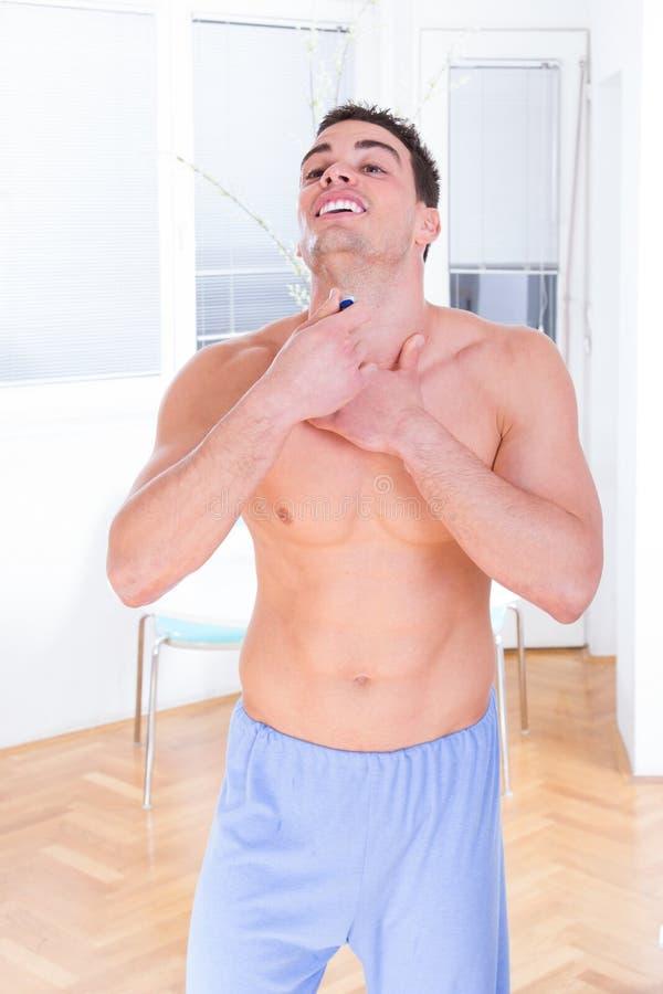 Uomo bello che usando sforzo per radere la sua barba immagini stock