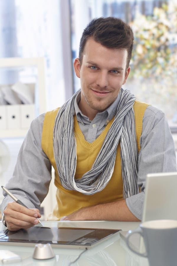 Uomo bello che usando sorridere del tavolo da disegno fotografia stock