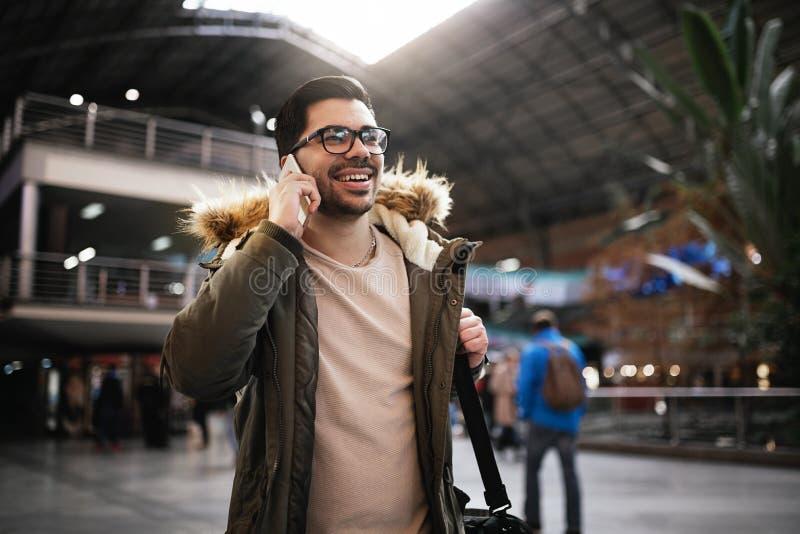 Uomo bello che utilizza cellulare nella stazione ferroviaria fotografie stock